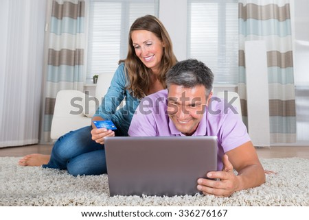 Portrait Of A Smiling Mature Couple Shopping On Laptop