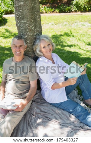 Portrait of a smiling mature couple sitting against a tree at the park