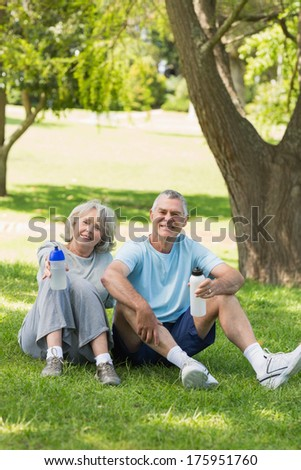 Portrait of a smiling mature couple sitting with water bottles at the park - stock photo