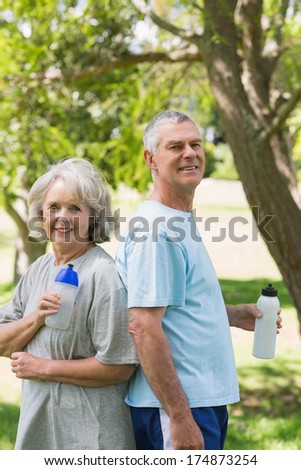 Portrait of a smiling mature couple standing with water bottles at the park - stock photo