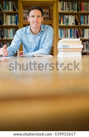 Portrait of a smiling mature male student studying at desk in the library