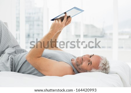 Portrait of a smiling mature man resting with digital tablet in bed at home