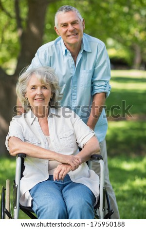 Portrait of a smiling mature man with woman sitting in wheel chair at the park - stock photo