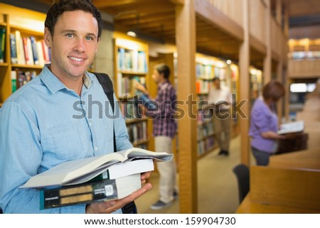 Portrait of a smiling mature student holding book with people in the background at a library