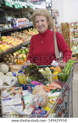 Portrait of a smiling mature woman doing grocery shopping in supermarket - stock photo