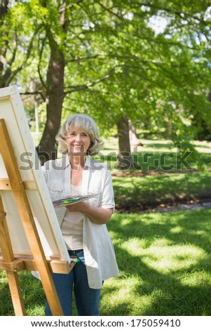 Portrait of a smiling mature woman painting on canvas in the park - stock photo