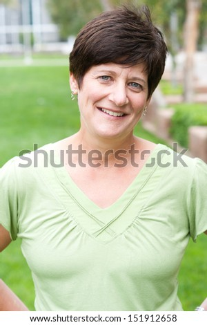 portrait of a smiling mature woman taken outside on campus - stock photo