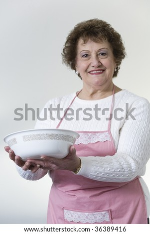 Portrait of a smiling mature woman with a bowl. - stock photo