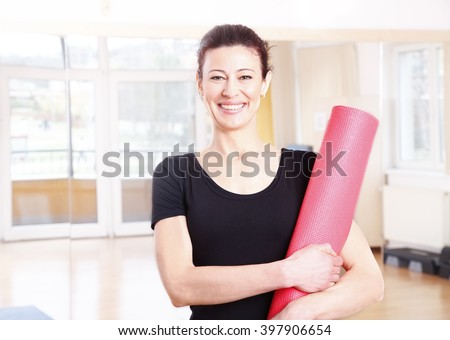 Portrait of a smiling middle age woman holding in her hand a yoga mat after doing yoga.