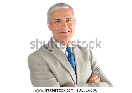 Portrait of a smiling middle aged businessman wearing a light tan suit with a blue necktie and his arms crossed. Horizontal over a white background. - stock photo