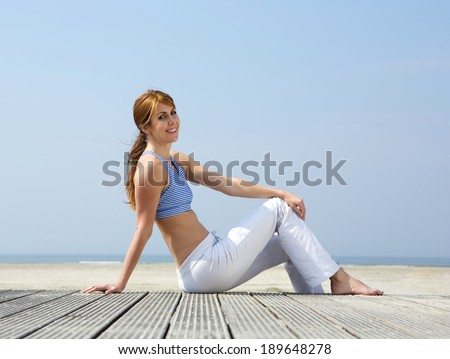 Portrait of a smiling middle aged woman relaxing at the beach  - stock photo