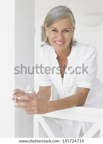 Portrait of a smiling middle aged woman with water glass leaning on verandah balustrade - stock photo