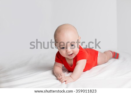 Portrait of a smiling 5 months baby boy in a red onesie lying down on a white blanket, holding hands together