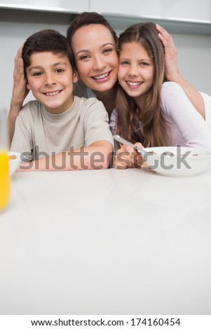 Portrait of a smiling mother with young kids in the kitchen at home - stock photo