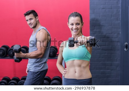 Portrait of a smiling muscular couple lifting dumbbells - stock photo