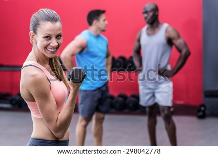 Portrait of a smiling muscular woman lifting a dumbbell - stock photo