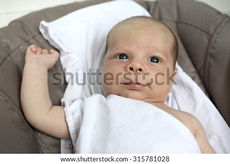 Portrait of a smiling newborn baby at home