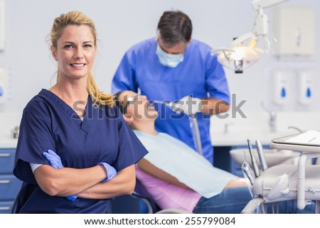 Portrait of a smiling nurse her arms crossed and dentist with the patient behind him - stock photo