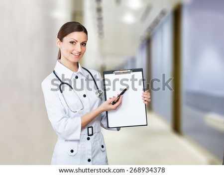 Portrait of a smiling nurse pointing to clipboard - stock photo