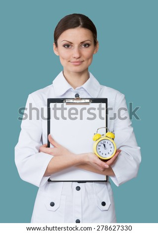 Portrait of a smiling nurse with a clipboard and a clock - stock photo