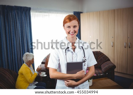 Portrait of a smiling nurse with seniors in a retirement home - stock photo