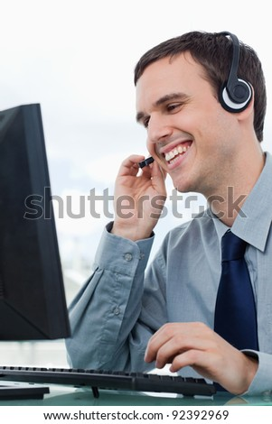 Portrait of a smiling office worker using a headset in his office - stock photo