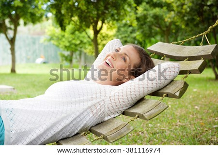 Portrait of a smiling older woman relaxing on hammock outdoors - stock photo