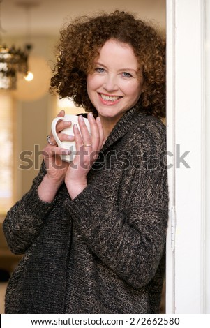 Portrait of a smiling older woman relaxing with a cup of tea at home - stock photo