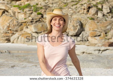 Portrait of a smiling older woman walking at the beach with hat - stock photo