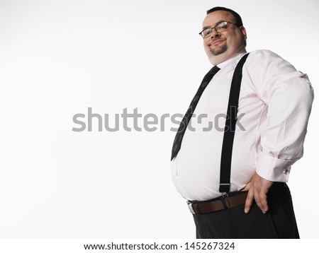 Portrait of a smiling overweight businessman standing with hand on hip against white background - stock photo