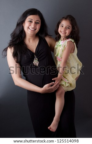 Portrait of a smiling, pregnant East Indian woman sitting with her daughter. The woman is wearing a formal gown. - stock photo