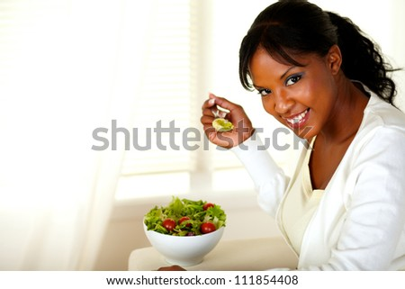 Portrait of a smiling pretty woman eating green salad and looking at you on light indoor background. With copyspace. - stock photo