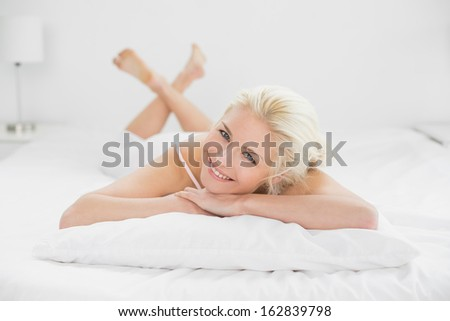 Portrait of a smiling pretty young woman resting in bed at home - stock photo