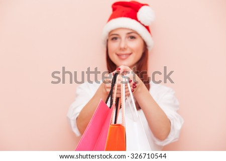 Portrait of a smiling redhead woman with shopping bags in Santa Claus hat on pink background