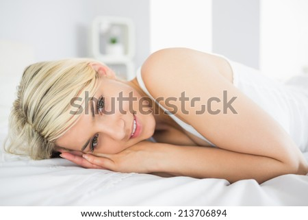 Portrait of a smiling relaxed young woman lying in bed at home - stock photo