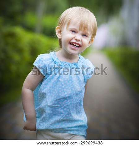 Portrait of a smiling running toddler girl in motion outdoors - stock photo
