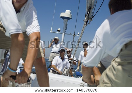 Portrait of a smiling sailor with crew on the sailboat deck against clear sky - stock photo