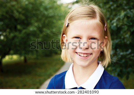 Portrait of a smiling schoolgirl in a blue dress - stock photo