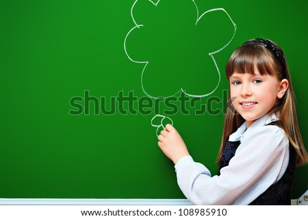 Portrait of a smiling schoolgirl in a classroom. - stock photo