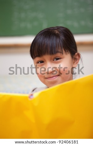 Portrait of a smiling schoolgirl reading in a classroom - stock photo