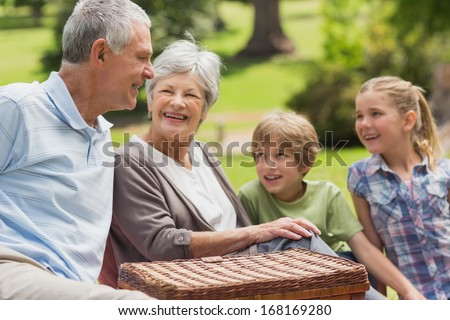Portrait of a smiling senior couple and grandchildren at the park - stock photo