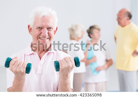 Portrait of a smiling senior man doing curls with weights, with his friends in the blurred background