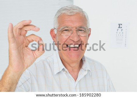 Portrait of a smiling senior man gesturing ok with eye chart in the background at medical office - stock photo