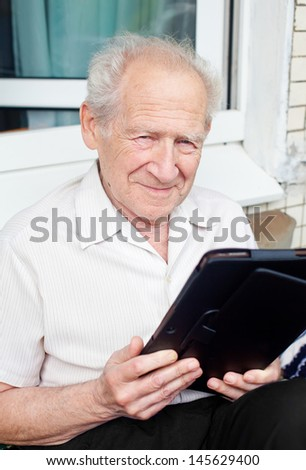 portrait of a smiling senior man with a touchpad PC - stock photo