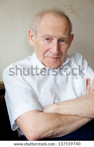 portrait of a smiling senior man with crossed arms - stock photo