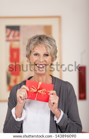 Portrait of a smiling senior woman holding gift coupon at home - stock photo