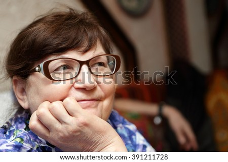 Portrait of a smiling senior woman in glasses - stock photo