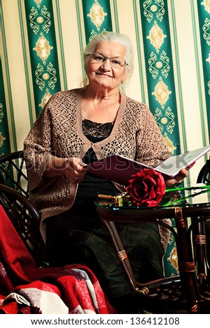 Portrait of a smiling senior woman reading a book at home. Old-fashioned style. - stock photo