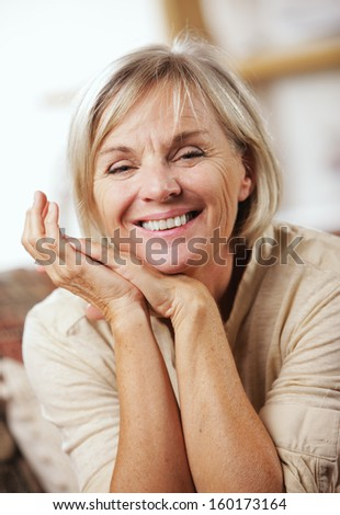 Portrait of a smiling senior woman sitting on couch - stock photo
