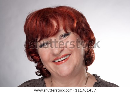 Portrait of a smiling senior woman. Studio shot over a light grey background.